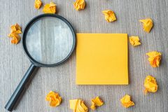 Note jaune vide avec le papier et la loupe emiettés sur le fond en bois de table Idée, vision, solution, stratégie, analyse photo libre de droits