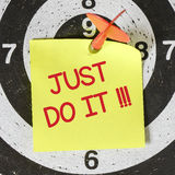 Note with just do it. Darts arrow with yellow sticky note with just do it pined on target center Stock Photography