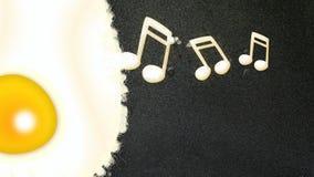 Note musicali che si formano da un uovo fritto fotografie stock