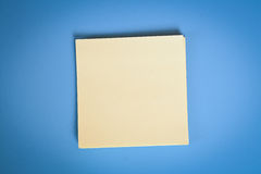 Note over blue background. One clean yellow note over blue background Stock Photos