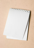 Note pad. With white page on beige background Royalty Free Stock Image