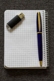 Note Pad with Blue Pen and Flash Drive. A series of photos with stationery items Royalty Free Stock Photo