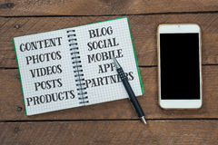 Note pad with content management considerations. Pencil, smart phone on wood table, high angle view Stock Photo