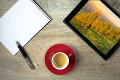 Note pad, cup of espresso coffee and ballpoint pen and tablet co. Mputer with vineyard picture Stock Photos