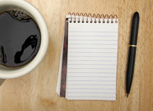 Note Pad Cup and Pen on Wood. Note Pad Coffee Cup and Pen on Wood Background Royalty Free Stock Photography