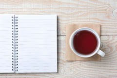 Note Pad and Cup of Tea. Closeup of an open notebook and a cup of hot tea on a rustic white wood table. High angle shot in horizontal format Stock Images