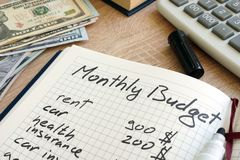 Note pad with monthly budget calculations and money. stock photos
