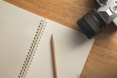 Note pad with an old camera. Vintage still life details, sunglasses, camera, pencil, paper Stock Image