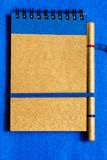 Note pad with pen. On a blue textured background Royalty Free Stock Photo
