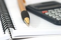 Note pad with pen and calculator. On it.Closeup. Shallow depth of field stock image