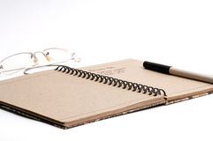 Note pad pen and glasses. In a white background Royalty Free Stock Images