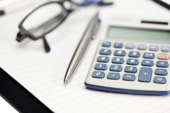 Note pad, pen, glasses and pocket calculator. On a white background Stock Photos
