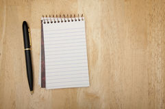 Note Pad and Pen on Wood. Background Royalty Free Stock Images