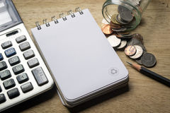 Note pad, pencil, coins and calculator Stock Photos