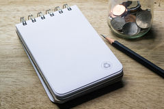 Note pad, pencil and coins Stock Photos