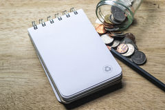Note pad, pencil and coins Stock Images