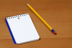 A note pad and pencil on a desk Stock Images