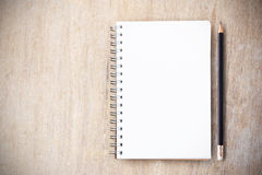 Note pad and pencil on wood table top view. Note pad and black pencil on wood table top view with copy space for any design Royalty Free Stock Image