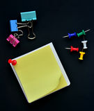 Note pad, Pushpin and Binder clip on black background Royalty Free Stock Photography