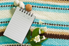 Note pad and white flower. For written record Stock Photo