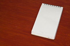 The note pad. On wood background Royalty Free Stock Images