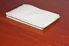 The note pad. On wood background Royalty Free Stock Photo