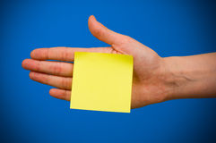 Note paper. Yellow empty note paper glued to the hand over blue background Stock Photo