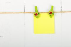 Note paper. One empty note paper hanging the clothesline, on wooden background, painted with white color Royalty Free Stock Photo