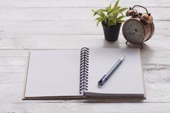 Note paper, book and pen with alarm clock, plant Royalty Free Stock Image