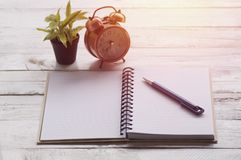 Note paper, book and pen with alarm clock, plant. On wood table Royalty Free Stock Photos