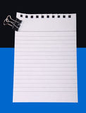 Note paper with clip. Writing note paper with with clip on blue-black background stock image