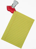 Note Paper and Clip. Red lips clip holding yellow note paper, isolated on white background Stock Images