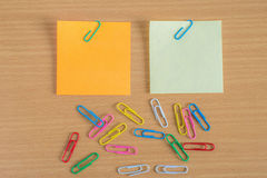 Note with a paper clip on wooden table Stock Photos