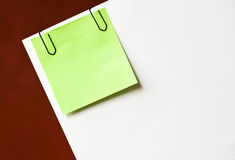 Note paper with clips. Green note paper with clips on white paper Royalty Free Stock Photo