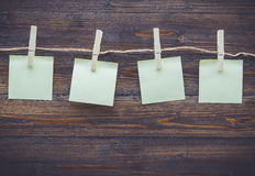 Note paper and cloth peg on wooden background Stock Image