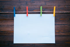 Note paper and colorful cloth peg on wooden background Royalty Free Stock Images