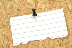 Note paper on cork board. Macro image. Royalty Free Stock Images