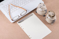 Note paper and eyeglasses on laptop. Note paper and eyeglasses on laptop and a couple of ceramic cat Stock Image