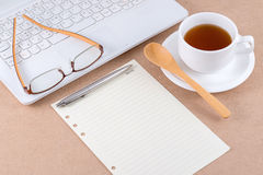 Note paper and eyeglasses on laptop. Note paper and eyeglasses on laptop with a cup of coffee Stock Images