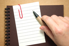 Note paper with hand and pen Royalty Free Stock Photography