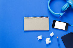 Note paper,headphones,smartphone,pencil,on blue backgro Royalty Free Stock Photo