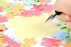 Note paper and puzzle with pen Royalty Free Stock Image