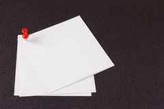 Note paper with red pin. On black. Clipping path included Stock Photo