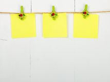 Note paper. Three empty note paper hanging the clothesline, on wooden background, painted with white color Stock Photos