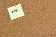 Note paper with word Happy birthday on brown notice cork board Stock Photos