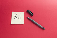 Note paper yes written black pen and red background Stock Images