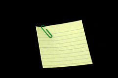 Note on Paperclip. Blank note held by a paperclip isolated on a black background Royalty Free Stock Photography