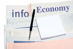 Note and pen, over stacked economy newspapers Stock Photography