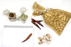 Note per conservare le ricette su un tavolo da cucina bianco Condimenti, ingredienti culinari - peperoni, aglio ed olio sulla tav immagine stock