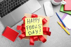 Note with phrase. `Happy Fool`s day` and gift box on office table. 1st April celebration Stock Image